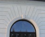 Наружное обрамление окна карнизом с замковым камнем и рустовой стены из ИБ